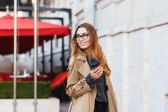 Retrato da mulher bonita que bebe o café afastado ao andar através da rua da cidade foto de stock