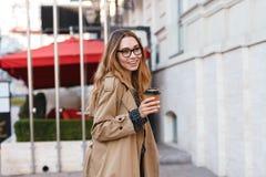 Retrato da mulher bonita que bebe o café afastado ao andar através da rua da cidade fotos de stock