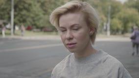 Retrato da mulher bonita que olha em linha reta na câmera mo seriamente lento vídeos de arquivo