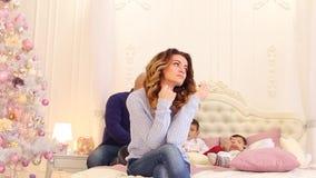 Retrato da mulher bonita que pensou sobre o futuro da família, sentando-se na cama contra o fundo do marido e video estoque