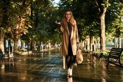 Retrato da mulher bonita que usa o telefone celular ao andar através da aleia vazia foto de stock royalty free