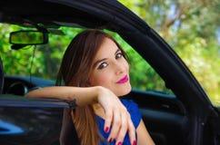 Retrato da mulher bonita que veste um vestido azul e que levanta dentro de um carro preto luxuoso em um roadtrip, a posição do ca Imagem de Stock Royalty Free