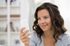 Retrato da mulher bonito feliz com o telemóvel que senta-se no sofá Foto de Stock Royalty Free