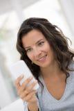 Retrato da mulher bonito feliz com o telemóvel que senta-se no sofá Imagens de Stock