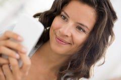 Retrato da mulher bonito feliz com o telemóvel que senta-se no sofá Fotografia de Stock Royalty Free