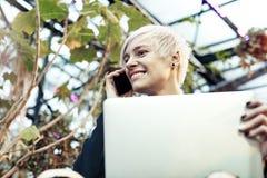 Retrato da mulher caucasiano do moderno com cabelo curto louro que fala pelo telefone celular Cara de sorriso da metade-cara, gar Imagens de Stock