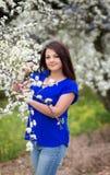 Retrato da mulher caucasiano nova no jardim de florescência da cereja, olhando em linha reta à câmera Fotos de Stock Royalty Free