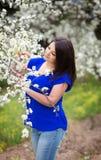 Retrato da mulher caucasiano nova no jardim de florescência da cereja, olhando a refeição matinal de florescência da árvore Imagem de Stock Royalty Free