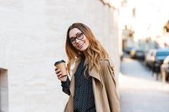Retrato da mulher caucasiano que bebe o café afastado ao andar através da rua da cidade fotos de stock