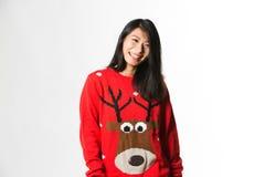 Retrato da mulher chinesa na camiseta do Natal que está na frente do fundo cinzento fotos de stock