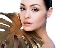 Retrato da mulher com a folha dourada grande perto da cara que olha a câmera Imagens de Stock Royalty Free