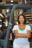 Retrato da mulher com o caminhão de empilhadeira no armazém Fotografia de Stock