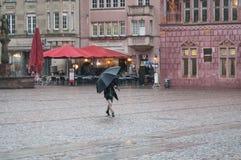 Retrato da mulher com o guarda-chuva que cruza um quadrado pavimentado na cidade Fotos de Stock Royalty Free