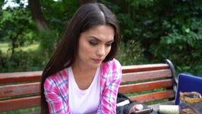 Retrato da mulher concentrada que senta-se no banco e que texting em seu telefone vídeos de arquivo