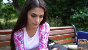 Retrato da mulher concentrada que senta-se no banco e que texting em seu telefone video estoque