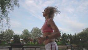 Retrato da mulher considerável que corre através do parque na manhã durante o nascer do sol video estoque