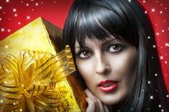 Retrato da mulher da beleza com o presente do Natal do ouro Fotografia de Stock