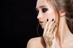 Retrato da mulher da beleza A composição e o tratamento de mãos profissionais com folha de ouro brilham, os olhos do smokey Cores fotografia de stock royalty free