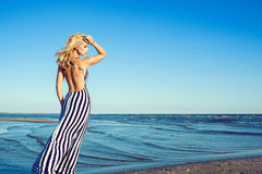 Retrato da mulher de cabelos compridos loura encantador no vestido listrado preto e branco longo com passeio traseiro despido ao  Foto de Stock