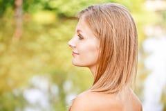 Retrato da mulher de encontro ao lago fotografia de stock