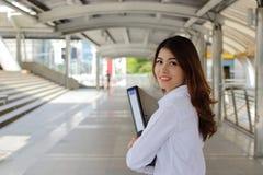 Retrato da mulher de negócio asiática atrativa que guarda dobradores do original em suas mãos em exterior público com fundo do es Imagens de Stock