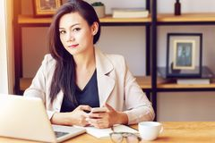 Retrato da mulher de negócio asiática bonita e segura na idade propícia para o trabalho usando a tecnologia do portátil do comput imagem de stock