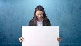 Retrato da mulher de negócio do sorriso com placa branca vazia no azul isolado Modelo fêmea com cabelo longo Fotos de Stock Royalty Free