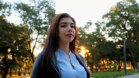 Retrato da mulher de negócio feliz nova na cidade Menina caucasiano bonita do estudante na blusa 'sexy' branca que está dentro filme