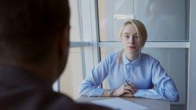Retrato da mulher de negócio na mesa, a que faz perguntas equipar oposto video estoque