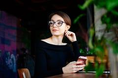 Retrato da mulher de negócio nova na cafetaria que guarda o telefone esperto em suas mãos imagens de stock royalty free