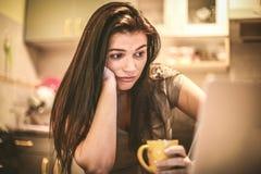 Retrato da mulher de negócio nova que trabalha em casa, usando o portátil imagem de stock royalty free