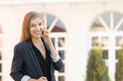 Retrato da mulher de negócio nova de sorriso que fala com telefone celular foto de stock royalty free