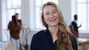 Retrato da mulher de negócio segura nova feliz do CEO com cabelo louro na roupa formal que olha a câmera no escritório filme