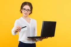 Retrato da mulher de negócio de sorriso nova bonita segura com o cartão de crédito de oferecimento do portátil no fundo amarelo imagem de stock royalty free