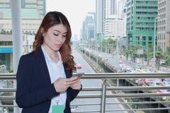 Retrato da mulher de negócios asiática nova atrativa que usa o telefone esperto móvel no fundo urbano da cidade Imagens de Stock Royalty Free