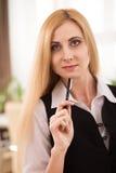 Retrato da mulher de negócios atrativa com a pena no escritório Fotos de Stock Royalty Free