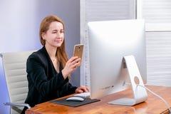 Retrato da mulher de negócios bem sucedida nova feliz no escritório Senta-se na tabela e lê-se um código de QR da exposição usand imagens de stock