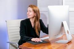 Retrato da mulher de negócios bem sucedida nova feliz no escritório Senta-se na tabela e mostra-se sua mão na exposição, trabalho fotografia de stock royalty free