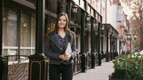 Retrato da mulher de negócios bonita nova que olha a câmera com sorriso fora, nas mãos que guardam uma tabuleta, lenta filme