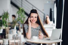 Retrato da mulher de negócios bonita que fala no telefone ao apreciar o café quente no café Fêmea atrativa adulta Foto de Stock Royalty Free
