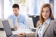 Retrato da mulher de negócios bonita que senta-se na mesa Fotografia de Stock