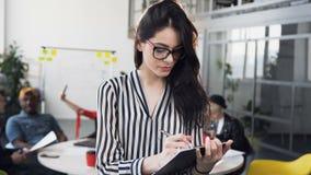 Retrato da mulher de negócios caucasiano atrativa na blusa com o cabelo longo que trabalha com documentos de papel, olhando ao video estoque
