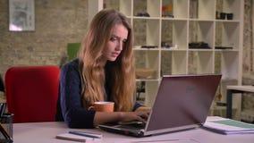 Retrato da mulher de negócios caucasiano loura bonita que trabalha com portátil e café bebendo no escritório filme