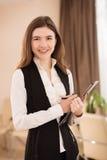 Retrato da mulher de negócios de sorriso nova com prancheta Imagem de Stock Royalty Free