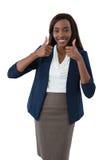 Retrato da mulher de negócios de sorriso que mostra os polegares acima Imagem de Stock Royalty Free