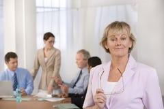Retrato da mulher de negócios e dos seus colegas. Imagem de Stock Royalty Free