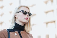 Retrato da mulher de negócios loura nova na cidade do outono A menina tem o olhar à moda, os óculos de sol e a perfuração do nari imagens de stock