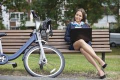 Retrato da mulher de negócios nova com o portátil que senta-se no banco no parque Fotografia de Stock Royalty Free