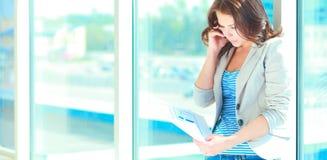 Retrato da mulher de negócios nova com telefone celular no corredor do escritório Imagens de Stock