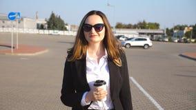Retrato da mulher de negócios nova com xícara de café que anda perto do auto estacionamento no dia ensolarado Mulher de negócio f filme